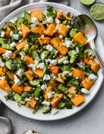 Overhead photo of a cantaloupe cucumber and feta salad on a large white serving plate.