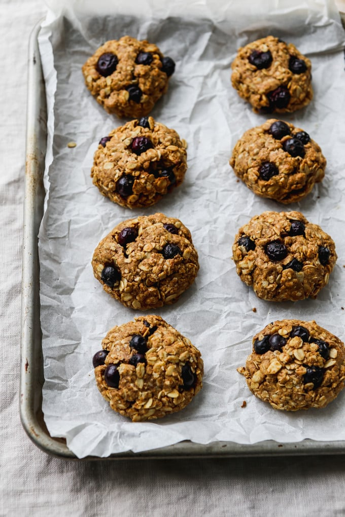 8 lemon blueberry oatmeal cookies on a parchment-lined baking sheet.