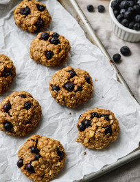 Lemon blueberry oatmeal cookies on a parchment-lined baking sheet.