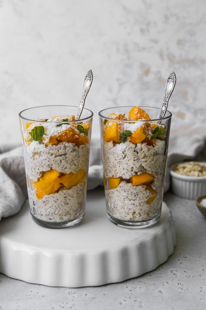 Straight on shot of two glasses filled with mango overnight oats.
