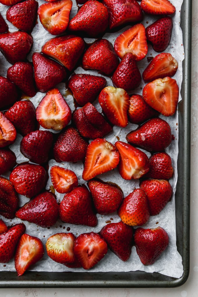 Overhead photo of sliced strawberries on a parchment-lined baking sheet.