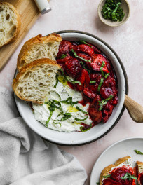 Overhead photo of a white bowl filled with whipped feta, roasted balsamic strawberries, and slices of toast.
