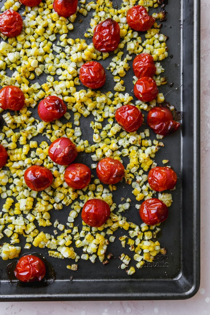 Overhead photo of roasted corn and cherry tomatoes on a baking sheet.