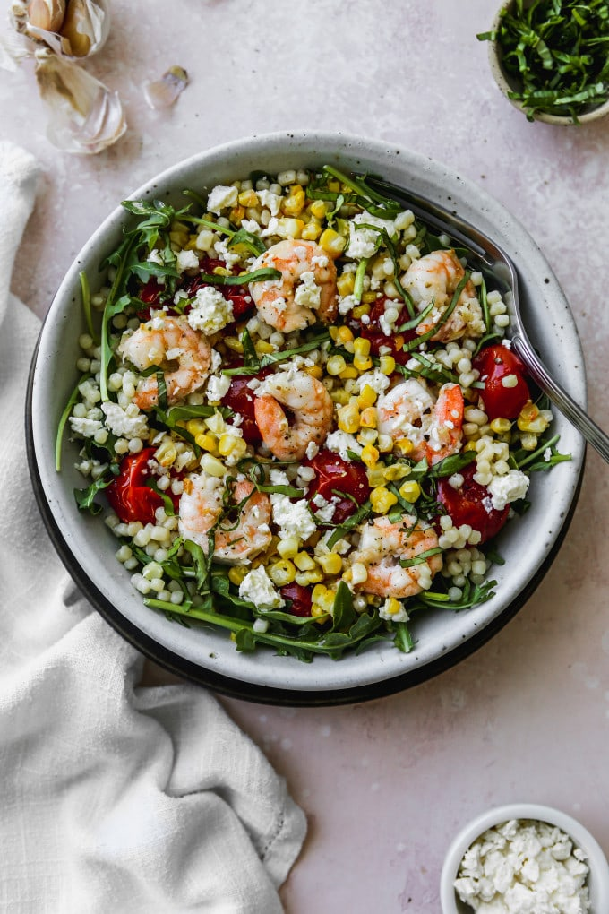 Overhead photo of arugula, couscous, roasted corn, tomatoes, and shrimp in a white bowl.