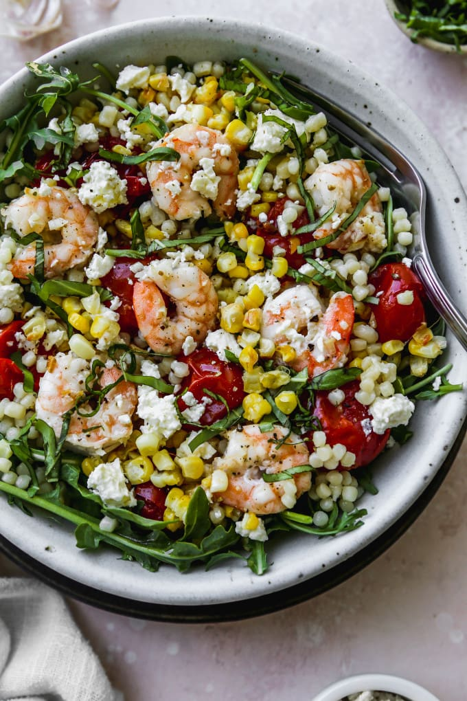 Closeup overhead photo of arugula, couscous, roasted corn, tomatoes, and shrimp in a white bowl.