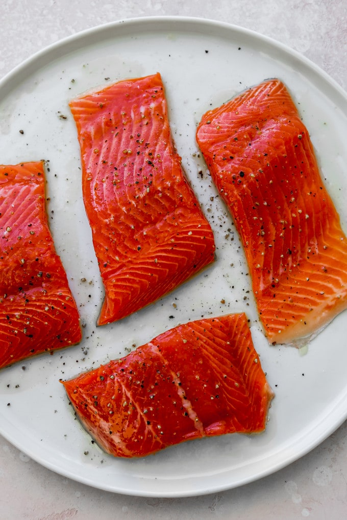Overhead photo of 4 pieces of uncooked salmon on a white plate.