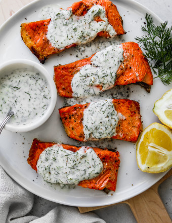Overhead photo of 4 pieces of grilled salmon topped with yogurt sauce on top of a white plate.
