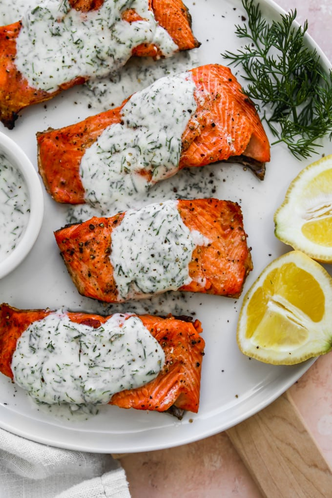Closeup photo of 4 pieces of grilled salmon topped with yogurt sauce on top of a white plate.