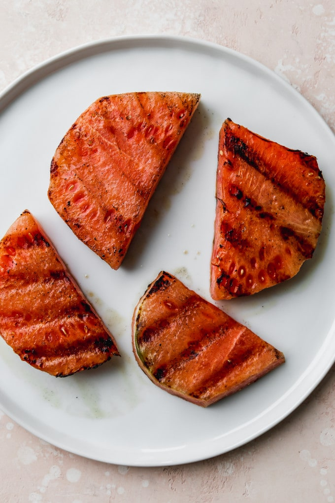 Overhead photo of pieces of grilled watermelon on a white plate.