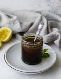 Glass jar of homemade balsamic vinaigrette dressing on a white plate.