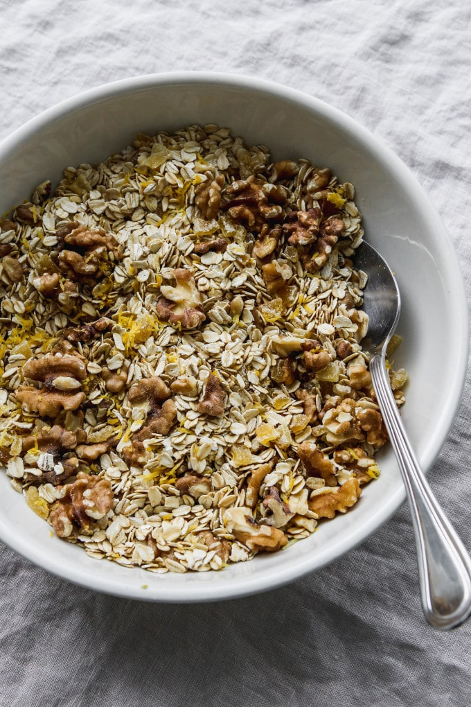 Overhead photo of a large white bowl filled with mixed dry ingredients for granola.