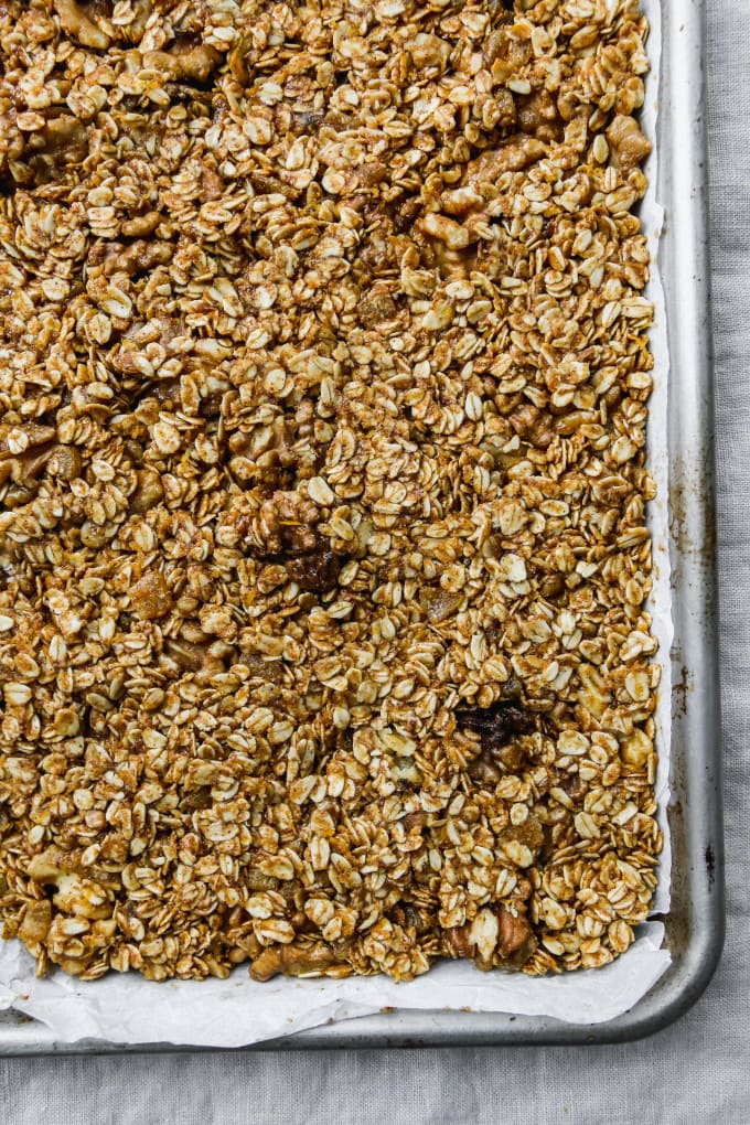 Overhead photo of uncooked granola pressed onto a parchment-lined baking sheet.