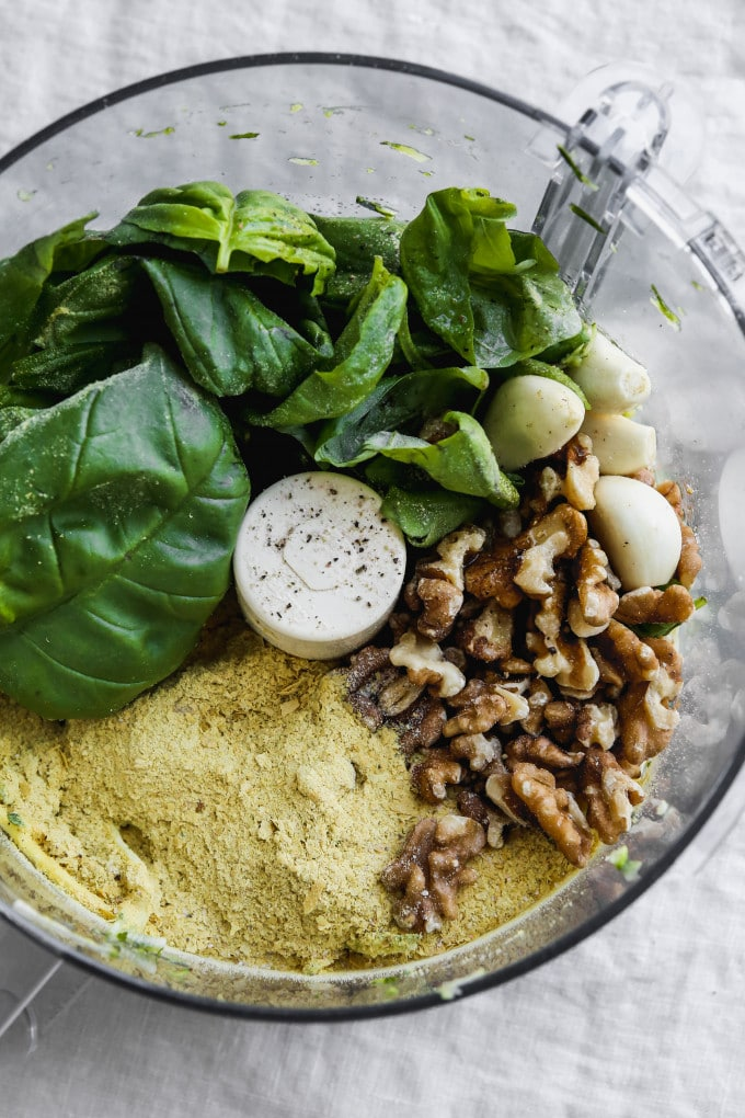 Basil, nutritional yeast, walnuts, and garlic cloves in a food processor.