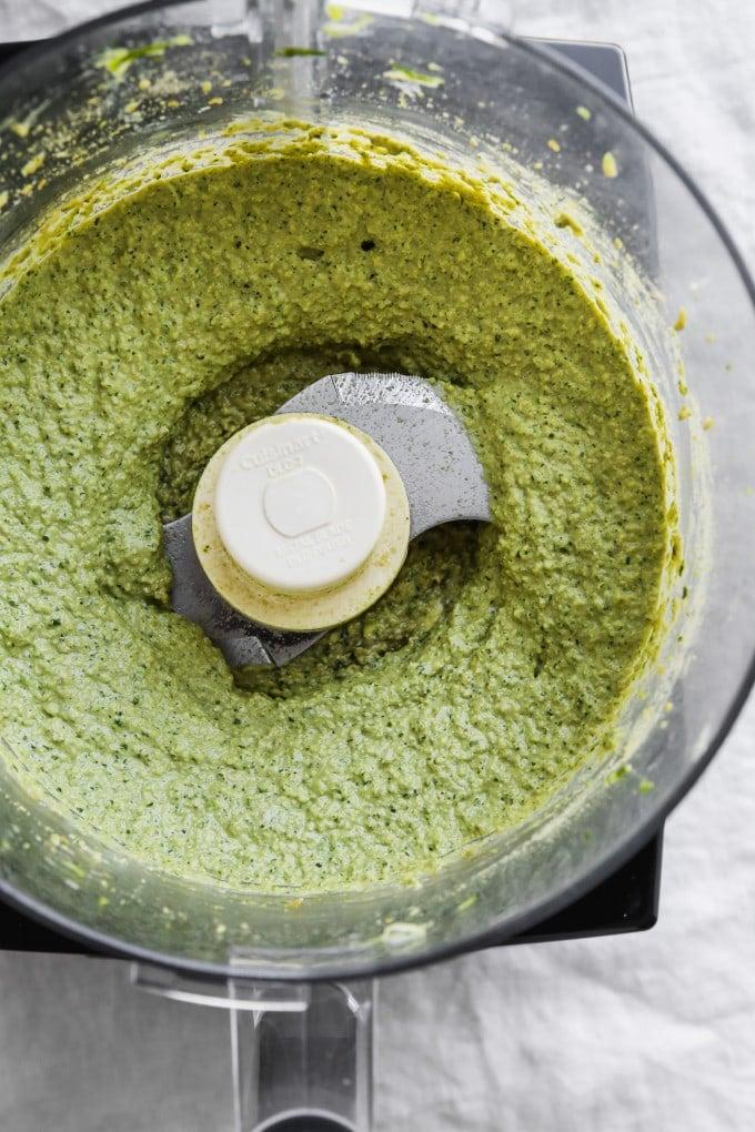 Overhead photo of creamy zucchini pesto in a food processor.