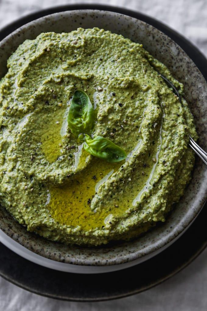 Overhead photo of creamy vegan zucchini pesto in a small grey bowl.