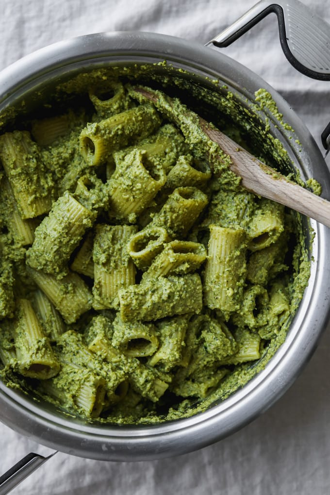Overhead photo of a large saucepan with rigatoni pasta tossed in zucchini pesto inside.