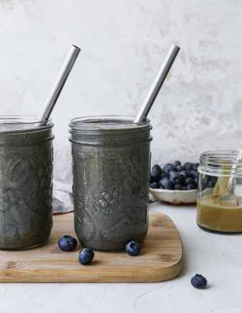 Straight on photo of two glasses filled with a blueberry banana tahini smoothie.