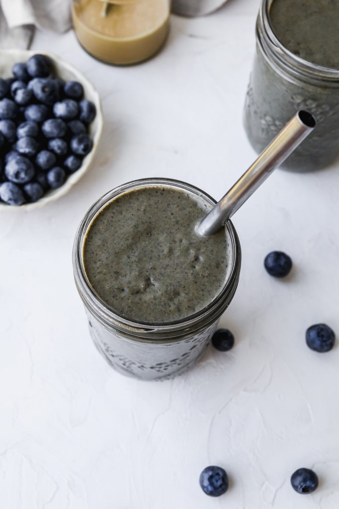 Overhead photo of a glass filled with a blueberry tahini smoothie recipe.