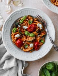 Overhead photo of a creamy goat cheese tomato spaghetti in a white bowl.
