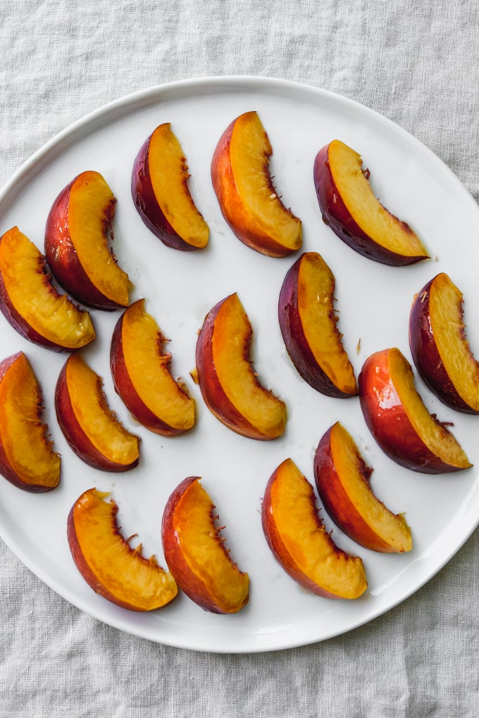 Overhead photo of sliced nectarines brushed in olive oil on a white plate.