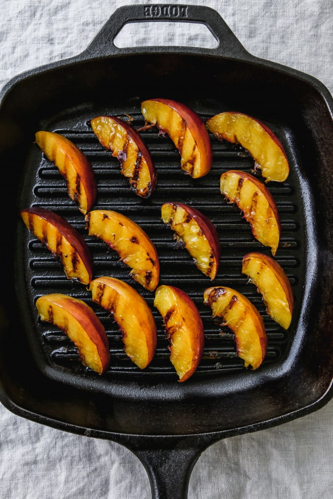 Overhead photo of grilled nectarine slices on a black grill pan.