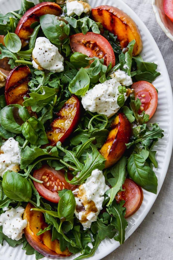 Closeup photo of a grilled nectarine, arugula, tomato, and burrata salad on a white serving dish.