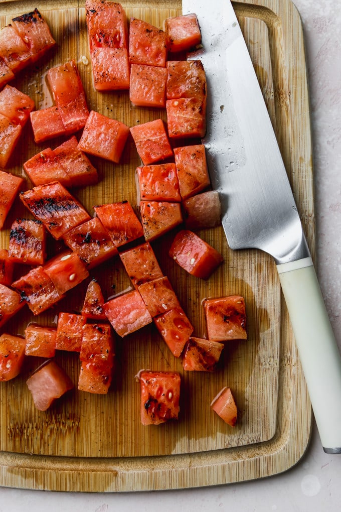Overhead photo of grilled watermelon sliced into chunks on a wood cutting board.