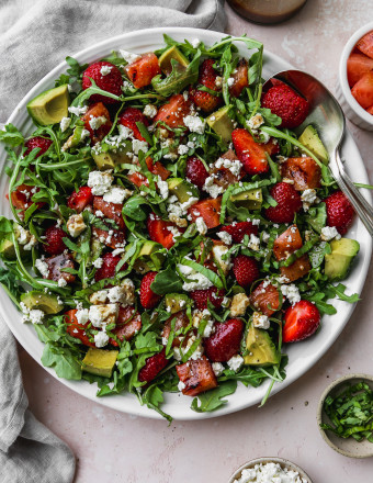 Overhead photo of a grilled watermelon salad with arugula, strawberries, avocado, feta, and basil on a white plate.