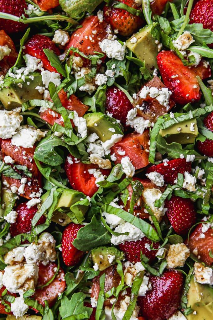 Closeup photo of a grilled watermelon salad with arugula, strawberries, avocado, feta, and basil.