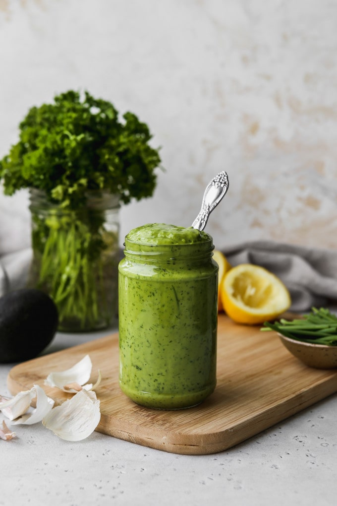 Straight on photo of a small glass jar filled with homemade avocado green goddess dressing.