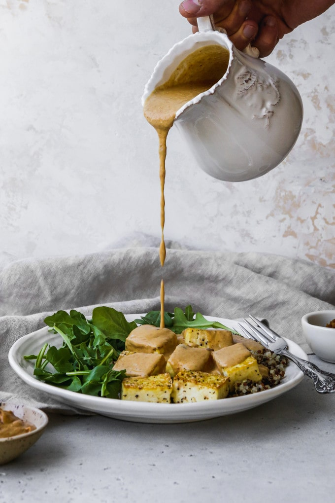 Straight on photo of miso peanut sauce being poured onto a plate of tofu.