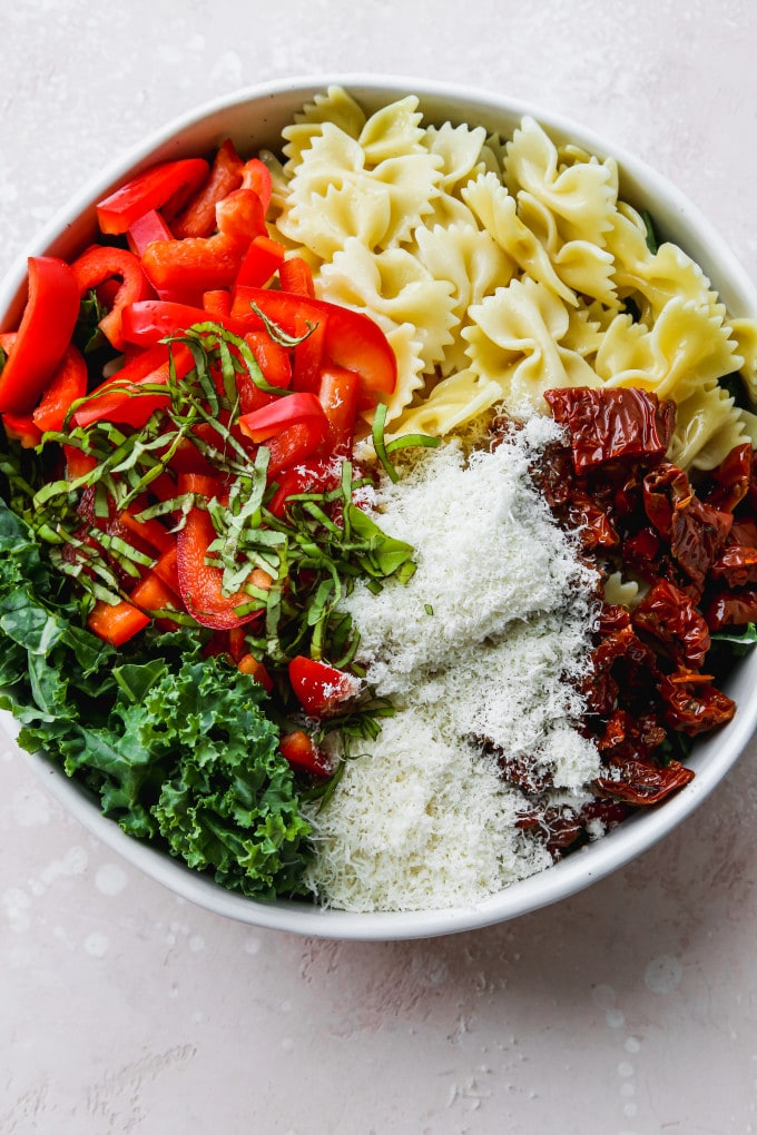 Overhead photo of kale, chopped bell peppers, bowtie pasta, sundried tomatoes, parmesan cheese, and basil in a large white bowl.