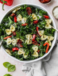 Overhead photo of a kale pasta salad with sundried tomatoes and peppers in a large white bowl.