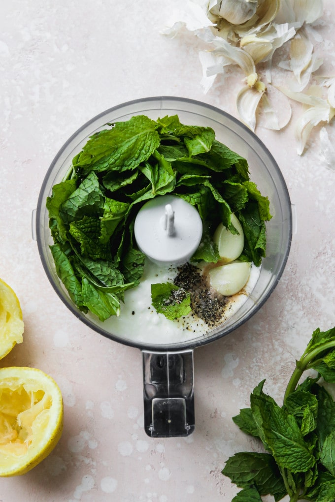 Overhead photo of a food processor with mint, yogurt, and garlic cloves inside.