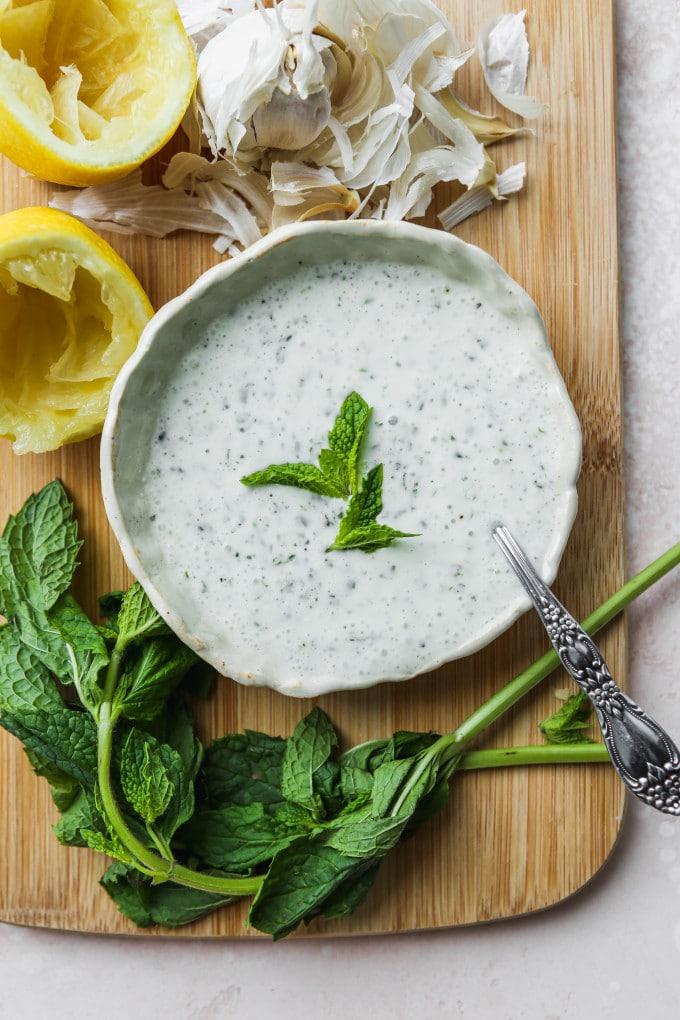Overhead photo of a mint yogurt sauce recipe in a small bowl on a wood cutting board.