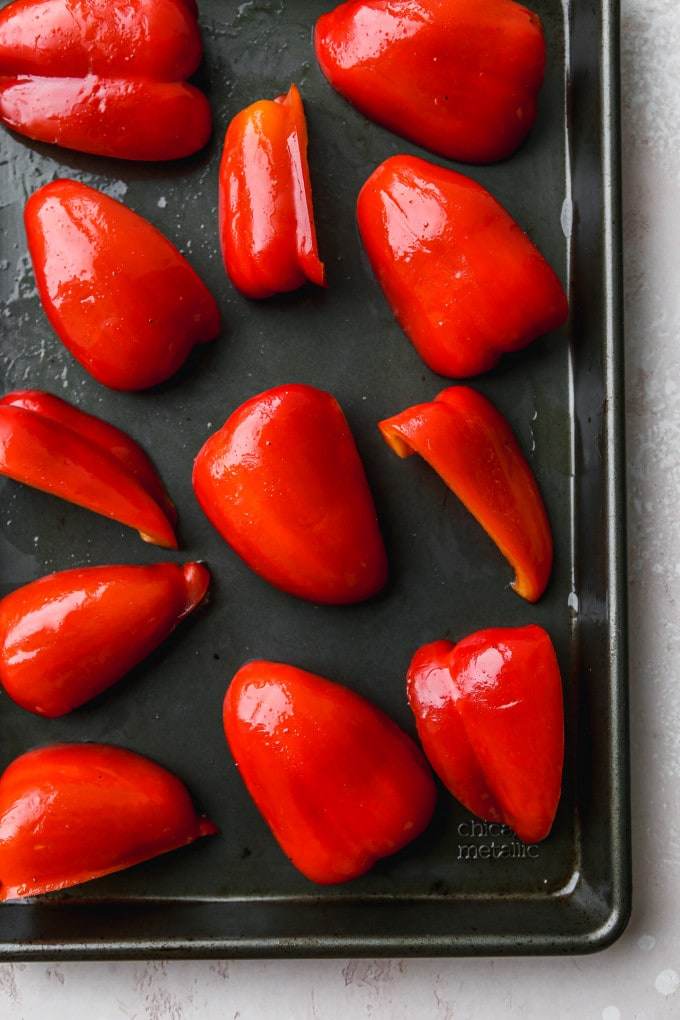 Overhead photo of quartered red bell peppers on a baking sheet.