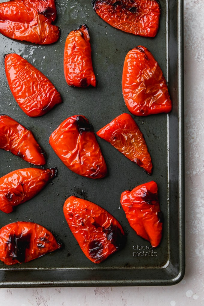 Overhead photo of roasted red peppers on a baking sheet.