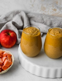 Overhead photo of two small glasses filled with a sweet potato and apple smoothie.
