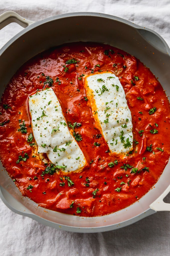 Overhead photo of two pieces of poached halibut in a pan of tomato coconut curry.