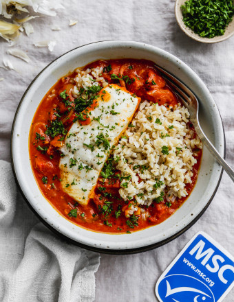 Overhead photo of poached halibut in a bowl of tomato coconut curry and rice.