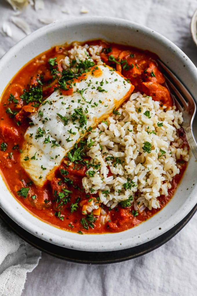 Closeup photo of poached halibut in a bowl of tomato coconut curry and rice.