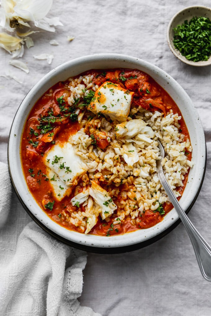 Overhead photo of poached halibut mixed together with tomato coconut curry and rice in a white bowl.