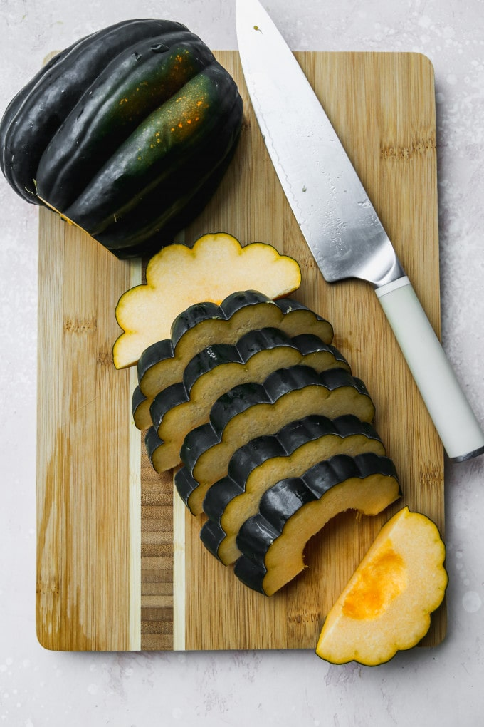 Overhead photo of an acorn squash sliced into rounds on a wood cutting board.