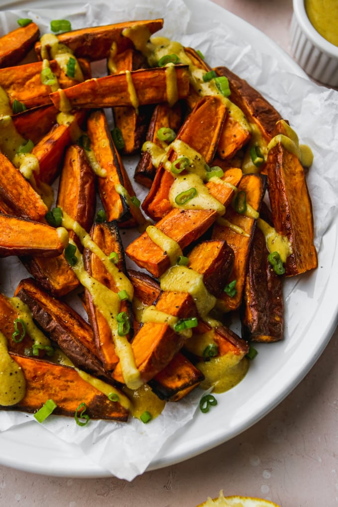 Closeup photo of roasted sweet potato wedges with curry tahini dressing drizzled on top.