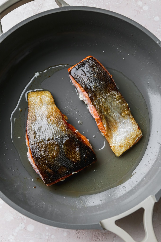 Overhead photo of salmon fillets cooking in a pan.