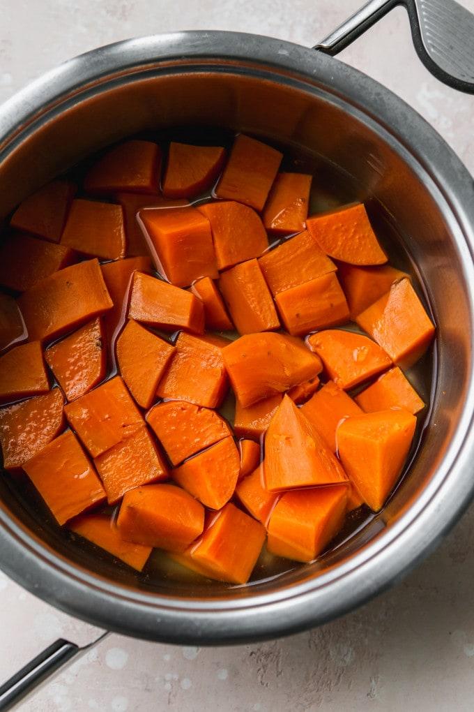 Overhead photo of chopped sweet potato chunks in a large pot.