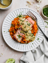 Overhead photo of salmon and sweet potato mash with miso coconut sauce on a white plate.