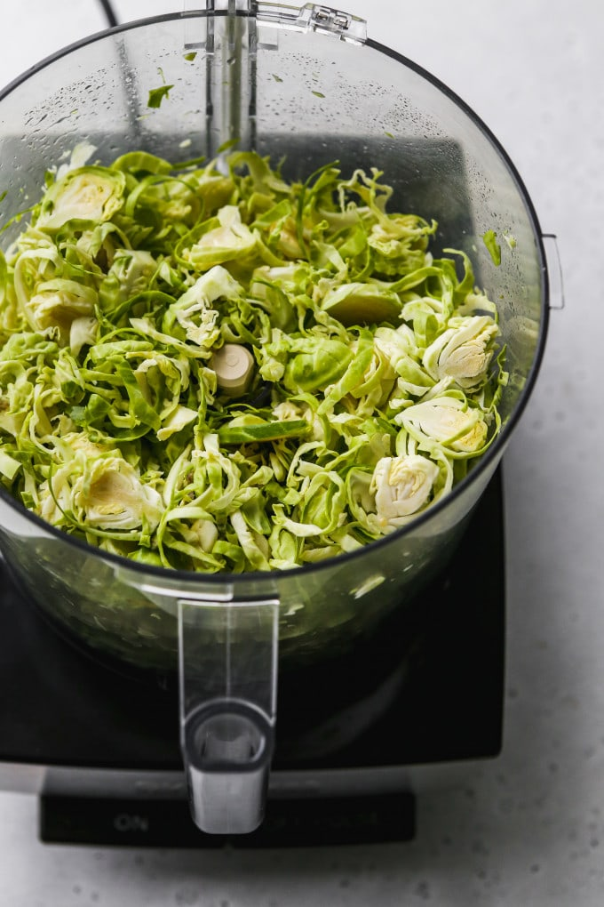 Overhead photo of shredded brussels sprouts in a food processor.
