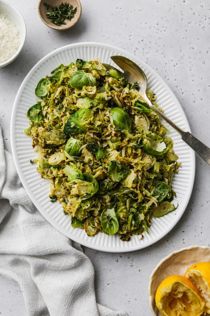 Overhead photo of sautéed shredded brussels sprouts on a white serving plate.