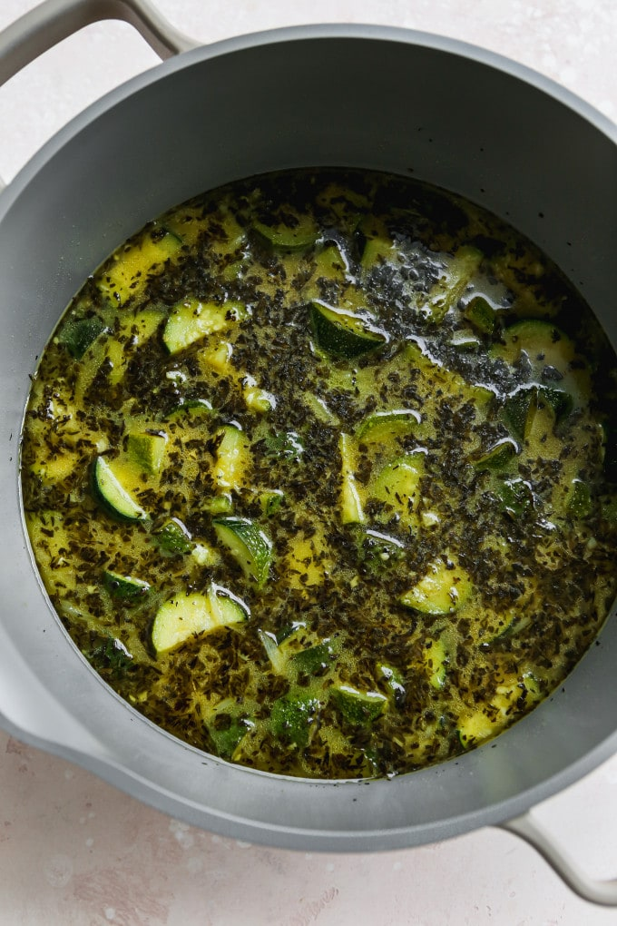 Overhead photo of zucchini, broth, and herbs in a pot.